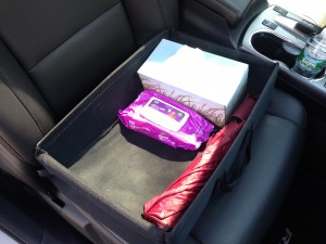 Use a car organizer with a rubber bottom and side handles to keep handy everything you need in the front of the car